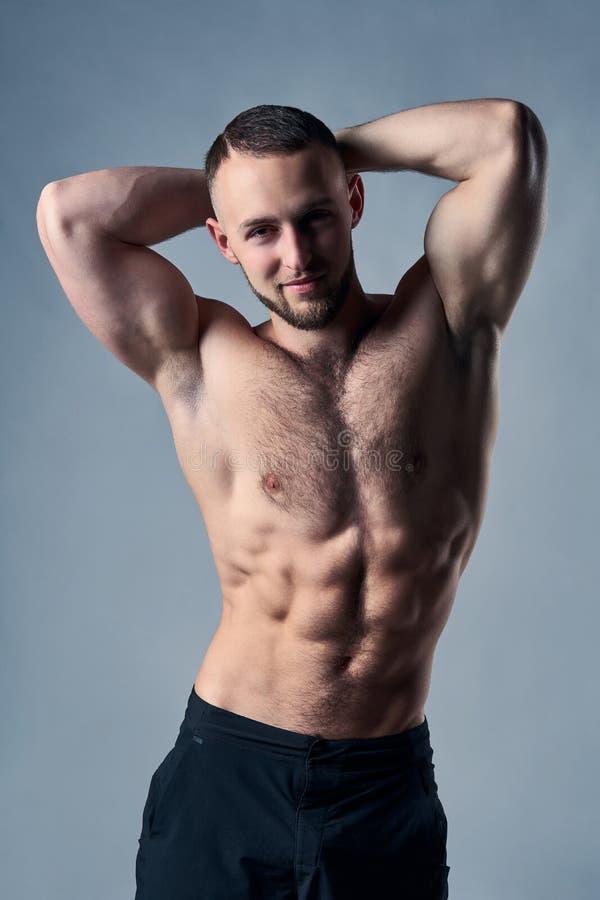 摆在用手的肌肉赤裸上身的人在头顶上 库存照片