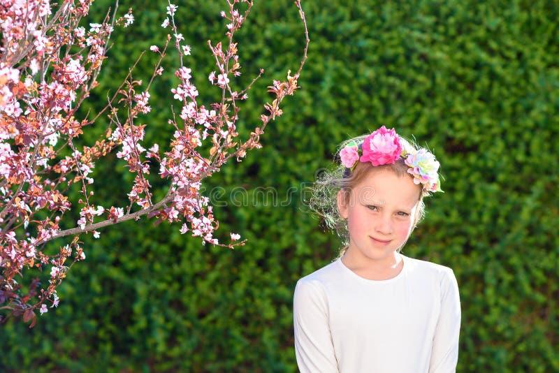 摆在用新鲜水果的逗人喜爱的女孩在晴朗的庭院里 免版税库存照片