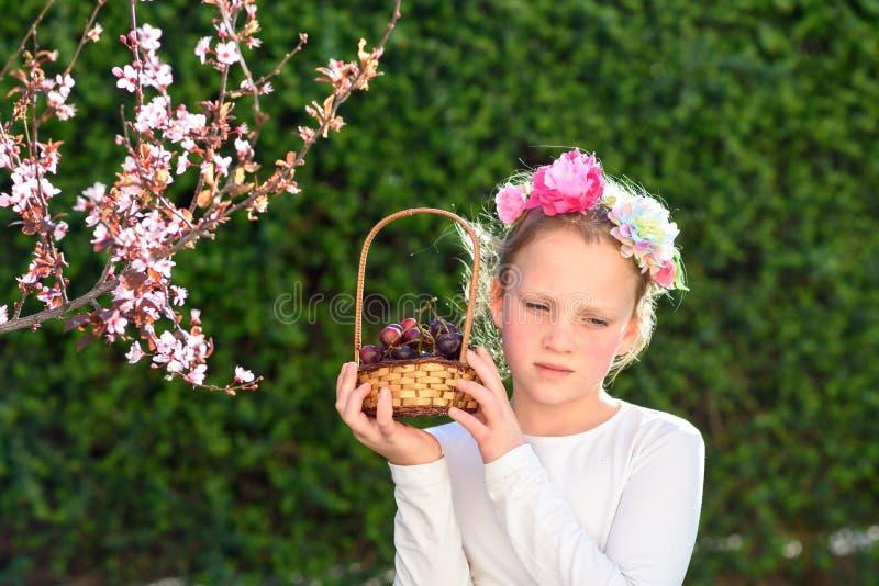摆在用新鲜水果的逗人喜爱的女孩在晴朗的庭院里 有葡萄篮子的女孩  免版税图库摄影