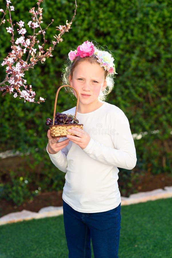摆在用新鲜水果的逗人喜爱的女孩在晴朗的庭院里 有葡萄篮子的女孩  免版税库存图片
