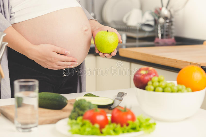 摆在用绿色苹果的孕妇被定调子的射击,当cooki时 免版税库存照片