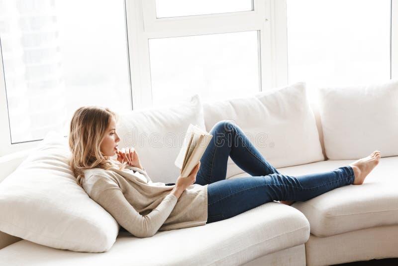 摆在白肤金发的妇女在家坐户内看书 免版税库存照片