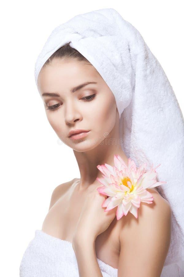 摆在白色毛巾的美丽的少妇。 免版税库存图片