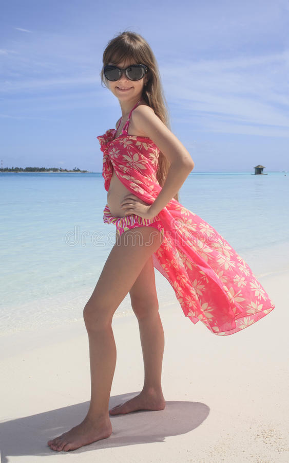 摆在白色沙滩的女孩 免版税库存图片