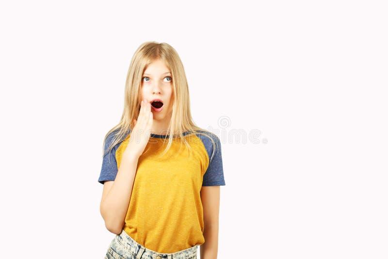 摆在白色的年轻美丽的少年模型女孩隔绝了显示情感表情的背景 库存照片