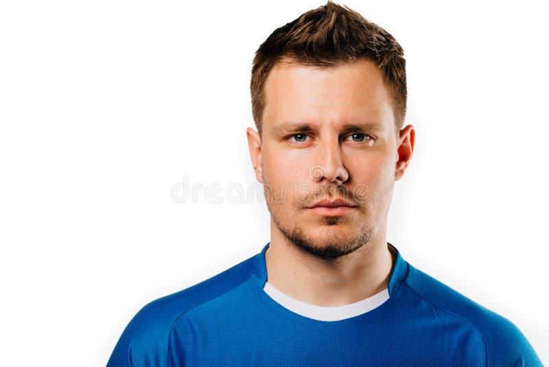 摆在白色的年轻英俊的足球运动员足球隔绝了背景 蓝色成套装备 库存图片