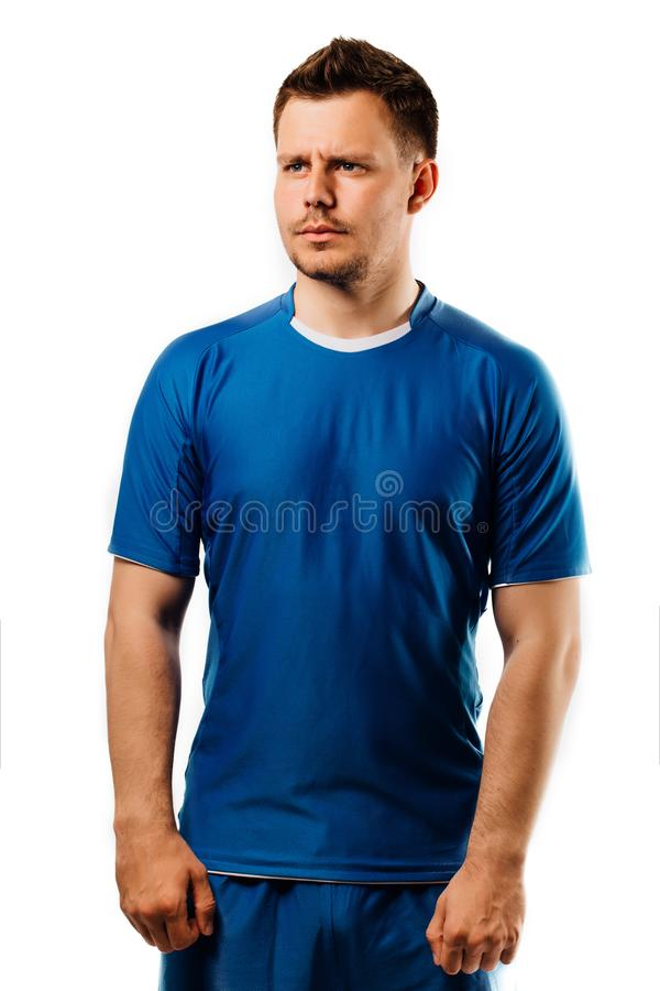摆在白色的年轻英俊的足球运动员足球隔绝了背景 蓝色成套装备 免版税库存图片