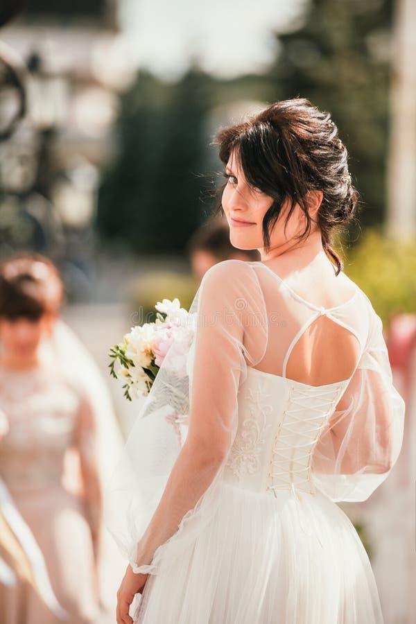 ?? 摆在白色礼服和面纱的年轻美丽的新娘 舒适,真正的情感 柔光夏天画象 ?? 免版税图库摄影