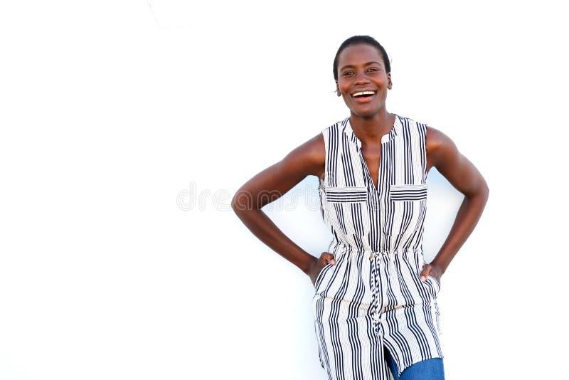 摆在白色背景和微笑的凉快的年轻非洲妇女 库存图片