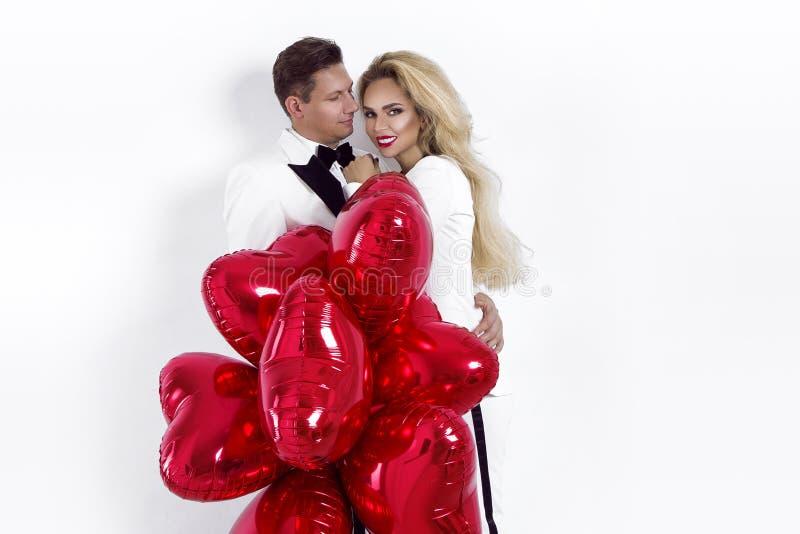摆在白色背景和拿着气球心脏的愉快的美好的夫妇 日s华伦泰 免版税库存照片