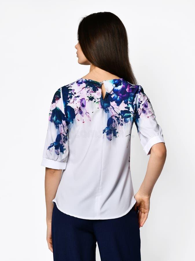 E 摆在白色衬衫女衬衫和蓝色牛仔裤的年轻美女 免版税库存图片