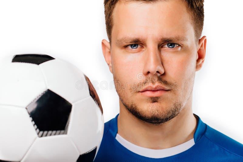 摆在白色被隔绝的年轻英俊的足球运动员足球特写镜头画象 免版税库存照片