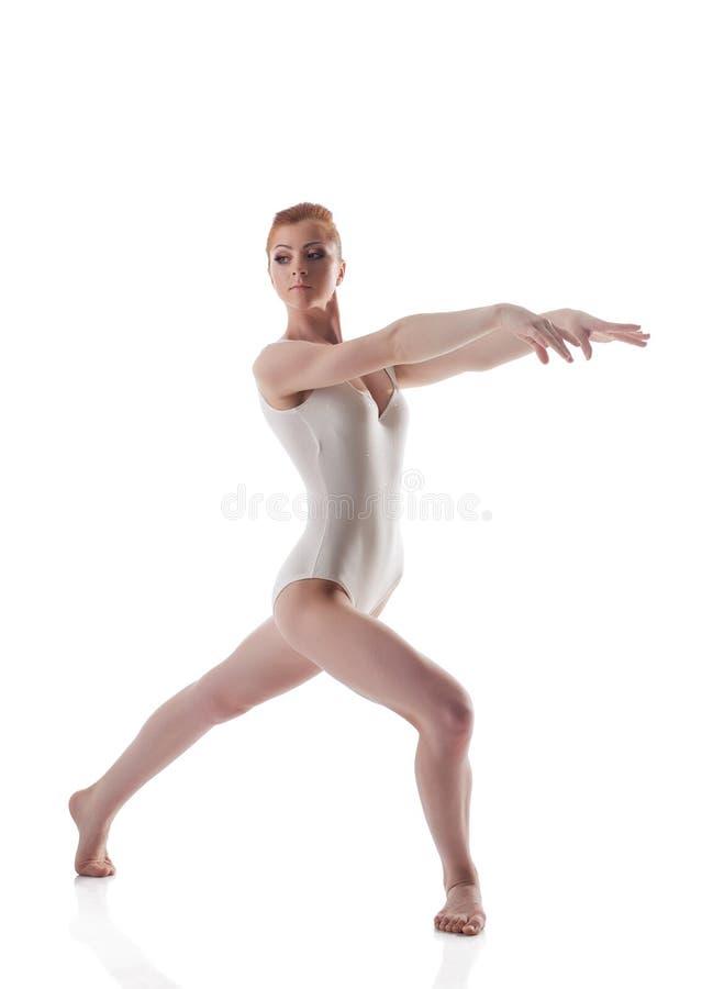 摆在白色紧身连衣裤的皮包骨头的红头发人体操运动员 免版税库存照片