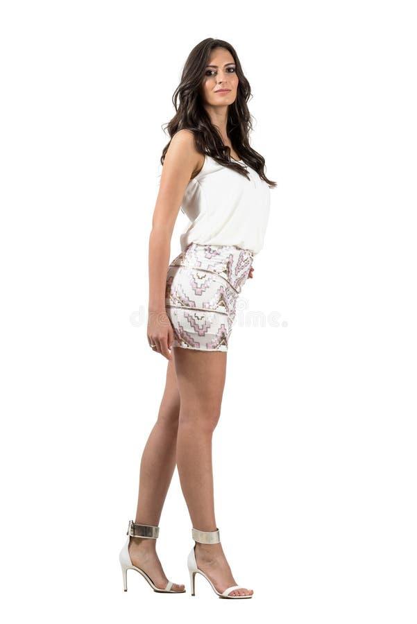 摆在短的微型的裙子的魅力时髦西班牙妇女看照相机 免版税库存照片