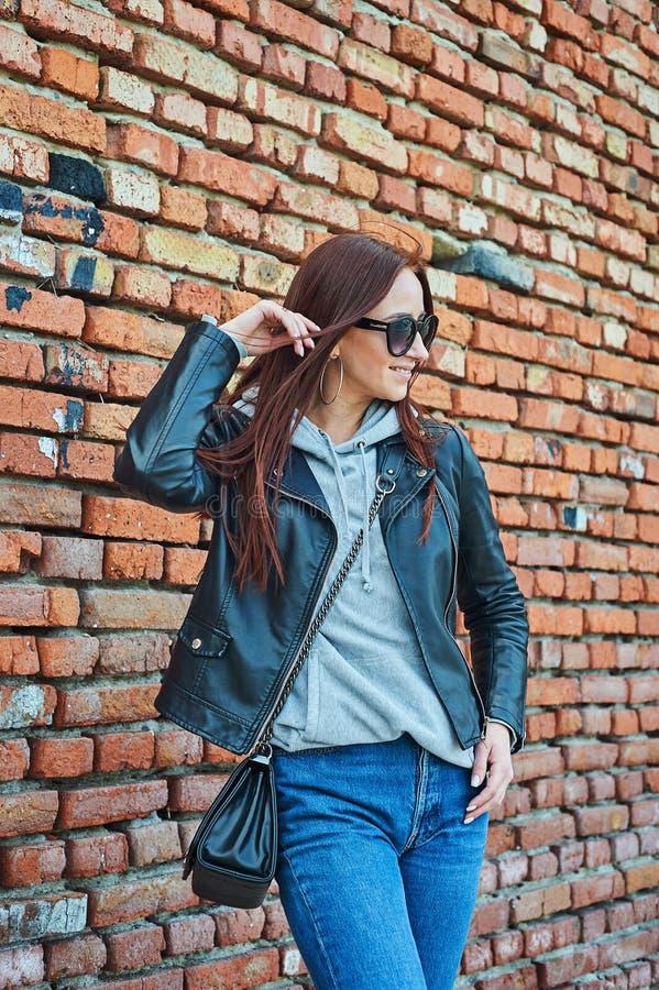 摆在砖墙附近的年轻红头发人妇女 库存图片