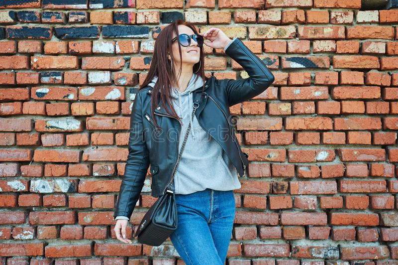 摆在砖墙附近的年轻红头发人妇女 图库摄影