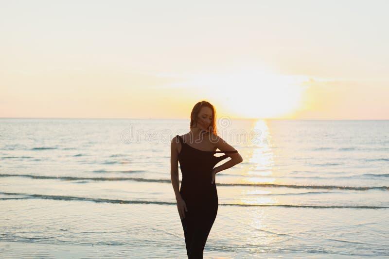 摆在礼服的可爱的妇女在海洋附近 库存图片