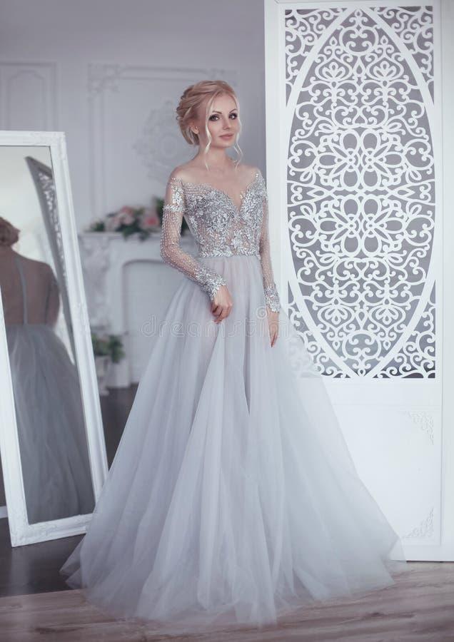 摆在礼服的婚礼流动的薄绸的礼服的美丽的新娘 免版税库存照片