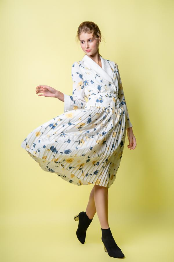 摆在礼服的美女在演播室 在一件明亮的便服的有吸引力的女性模型 免版税库存图片