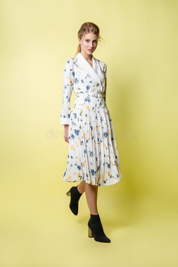 摆在礼服的美女在演播室 在一件明亮的便服的有吸引力的女性模型 库存照片