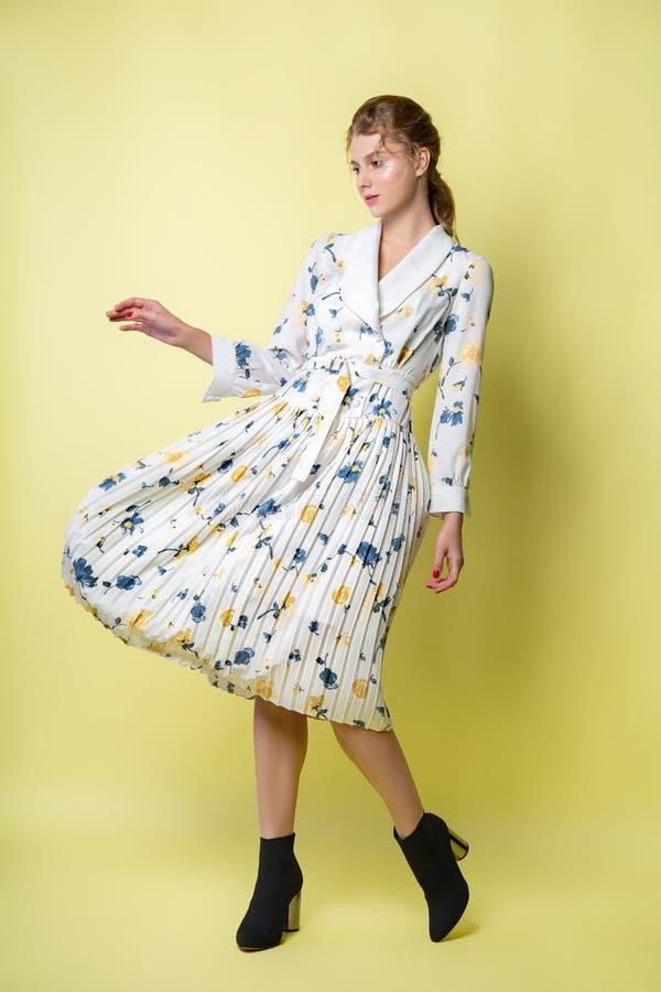 摆在礼服的美女在演播室 在一件明亮的便服的有吸引力的女性模型 图库摄影
