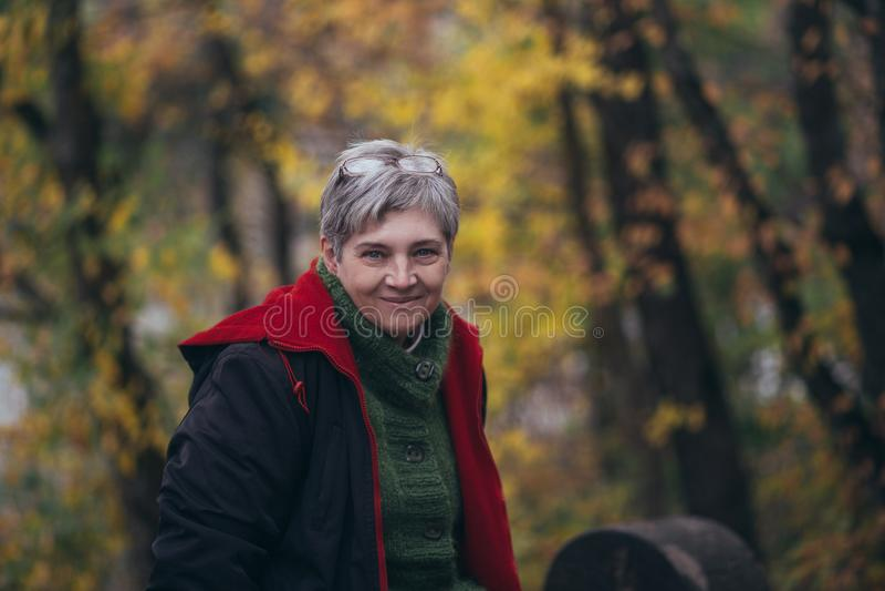 摆在秋天公园的资深妇女 免版税库存图片