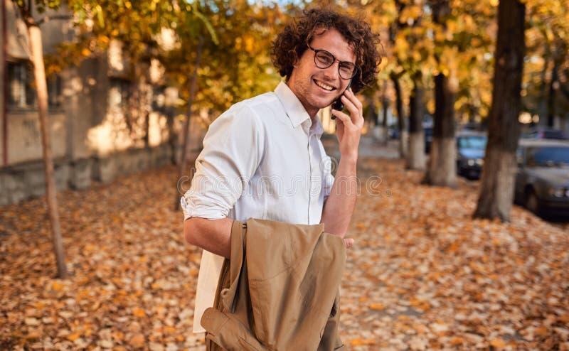 摆在秋天街道上的年轻英俊的商人,当走户外和使用智能手机为叫时 微笑的人与 免版税库存图片