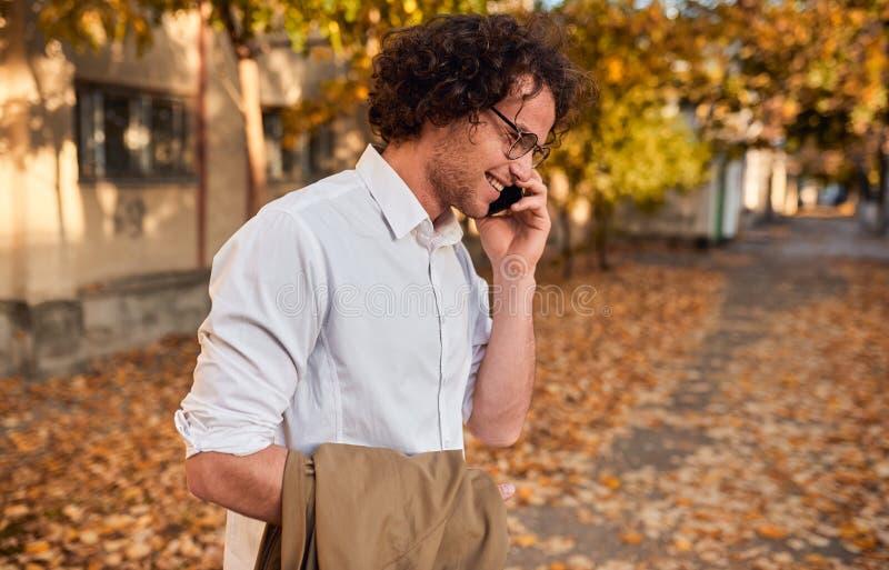摆在秋天街道上的英俊的商人侧视图射击,当走户外和使用智能手机为叫时 库存照片