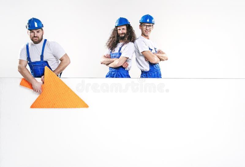 摆在空的白板旁边的三位英俊的工匠 免版税图库摄影