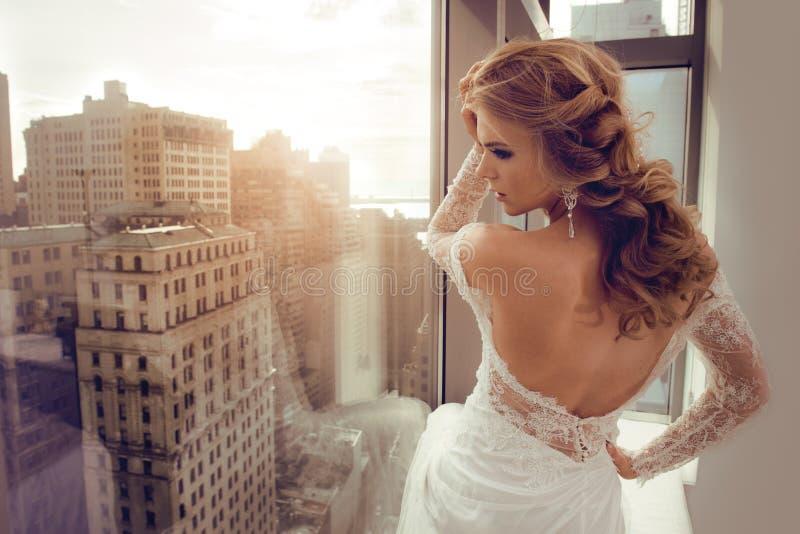 摆在窗口附近的婚礼礼服的美丽的年轻新娘 库存图片