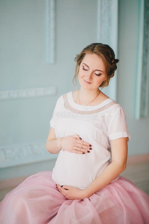 摆在窗口附近的年轻美丽的孕妇 免版税库存图片