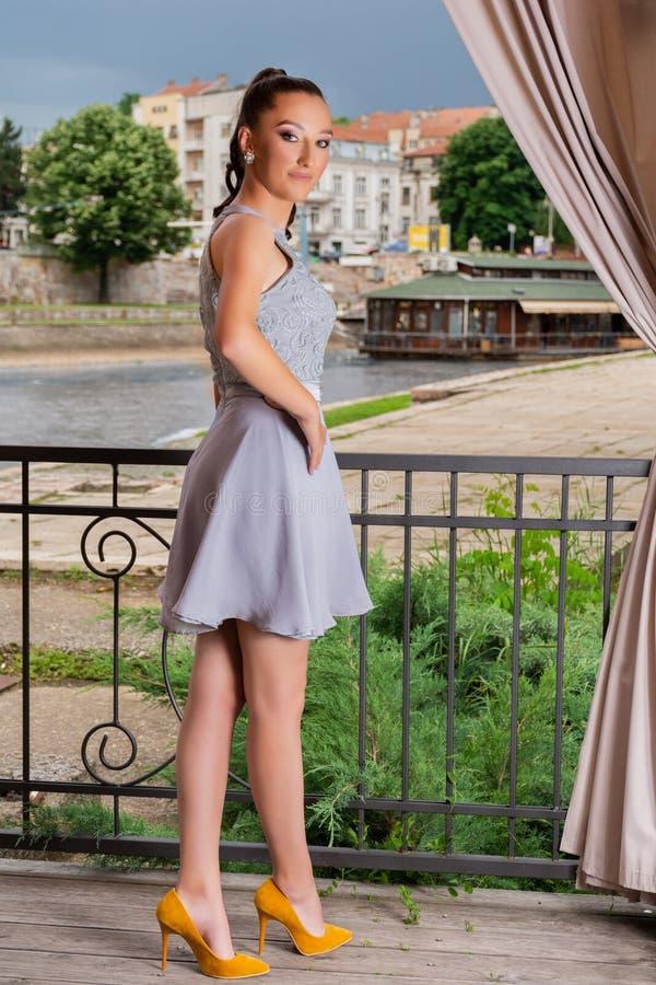 摆在篱芭前面的灰色短的礼服的典雅的愉快的女孩在餐馆庭院里 免版税库存照片