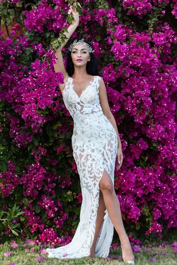 摆在紫罗兰色花卉背景的女孩 免版税库存图片
