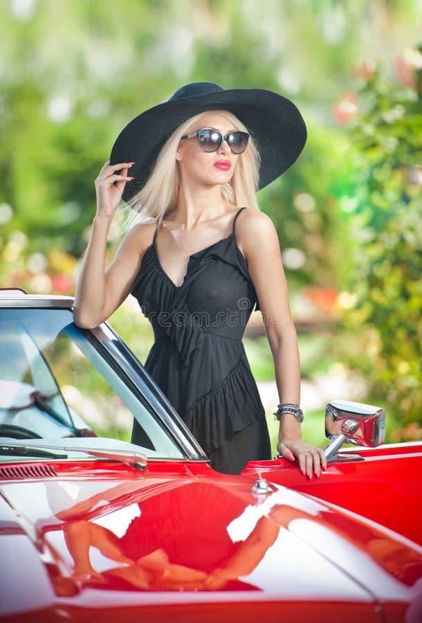 摆在红色减速火箭的汽车附近的时髦的白肤金发的葡萄酒妇女室外夏天画象  时兴的可爱的公平的头发女性 库存图片