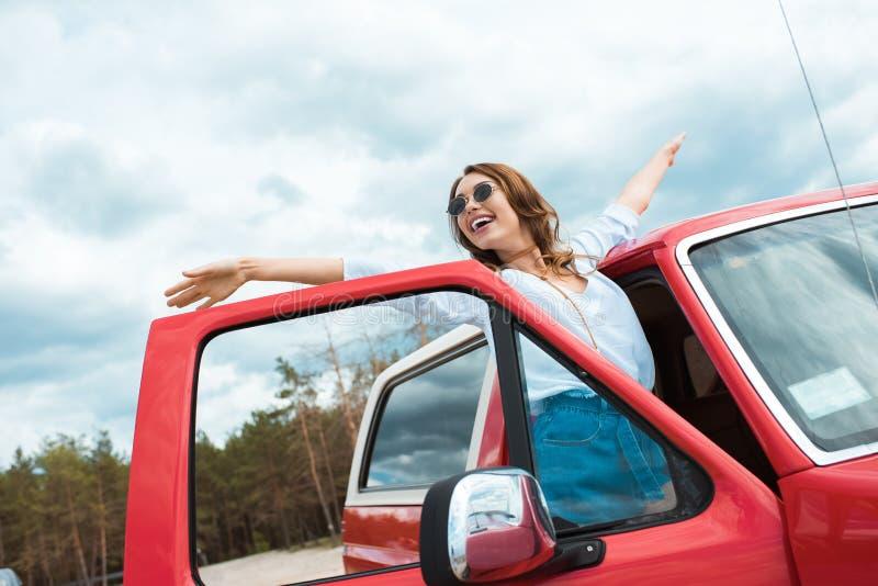 摆在红色汽车附近的太阳镜的激动的年轻女人 免版税库存照片