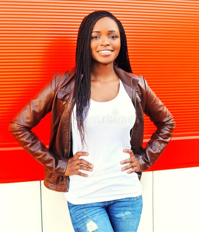 摆在红色的城市的夹克的美丽的非洲妇女 免版税库存照片