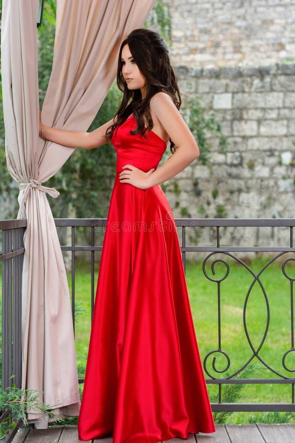 摆在红色的礼服的迷人的女孩和在餐馆庭院里握在臀部的一只手在铁篱芭和帷幕前面 库存照片