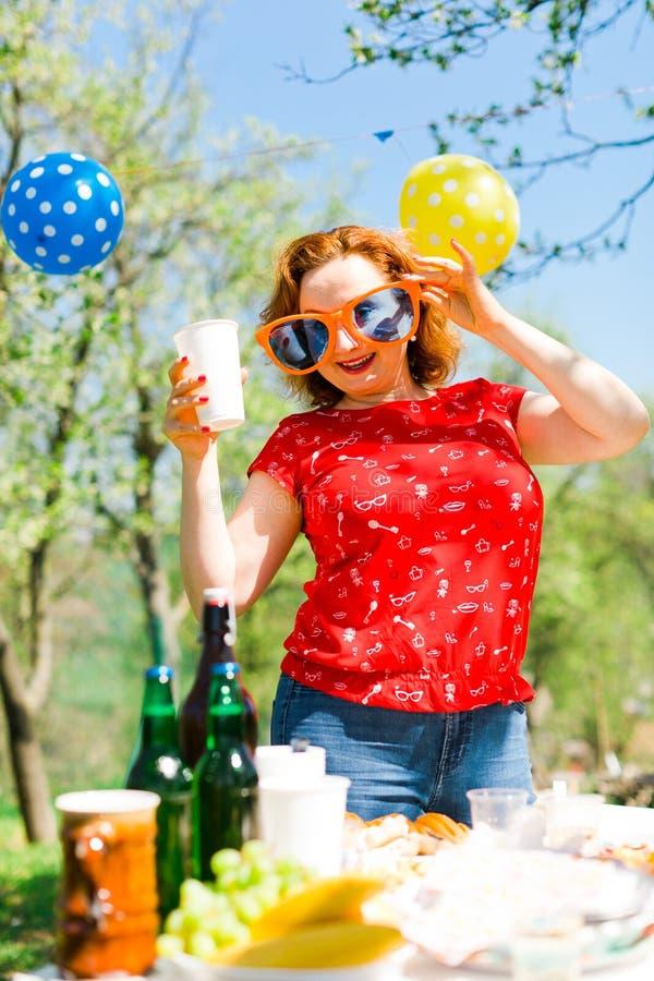 摆在红色礼服和大滑稽的太阳镜的妇女在庭院pa 免版税库存图片