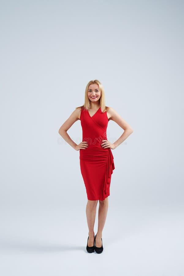 摆在红色礼服的年轻成人白肤金发的妇女在演播室 免版税库存图片