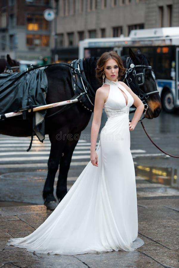 摆在纽约街道的长的白色婚礼礼服的美丽的妇女新娘 库存图片