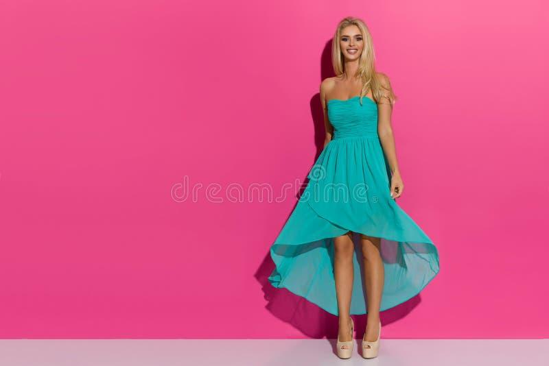 摆在绿松石礼服和高跟鞋的愉快的美丽的白肤金发的妇女 免版税库存照片