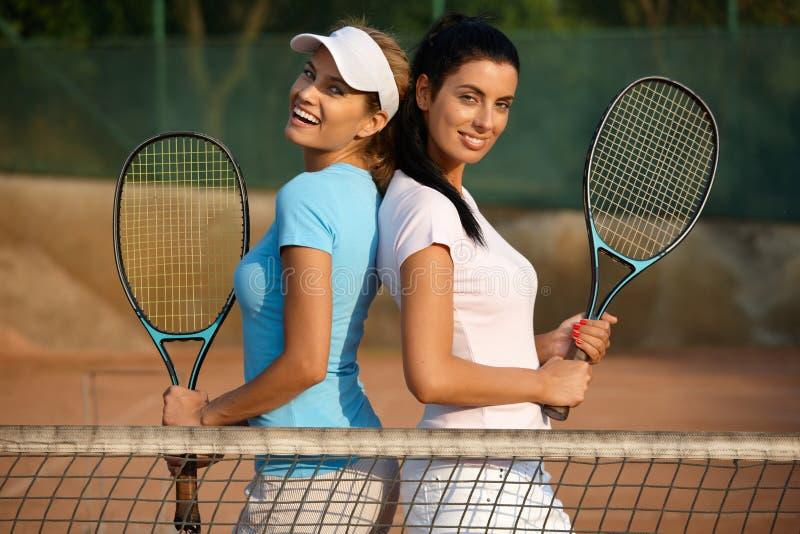 摆在网球场微笑的俏丽的女孩 免版税图库摄影