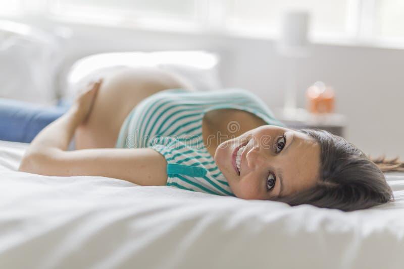 摆在美丽的孕妇,当在家时躺在床上 免版税图库摄影