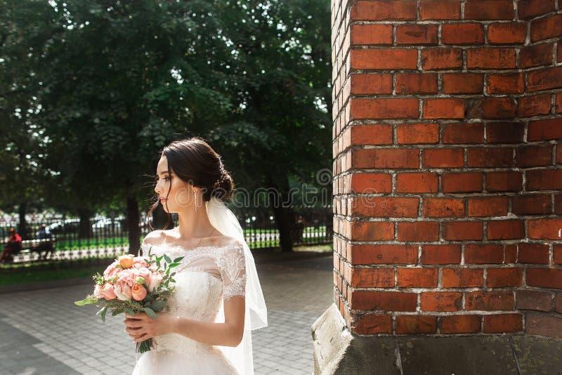 摆在老哥特式教会附近红色墙壁的美丽的新娘  免版税库存图片