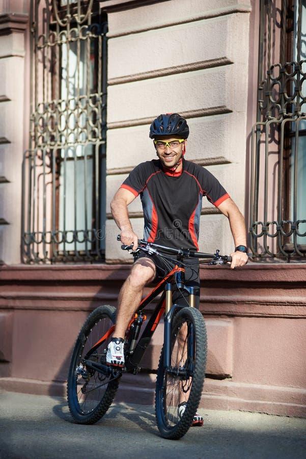 摆在老城市墙壁附近的骑自行车者 库存图片
