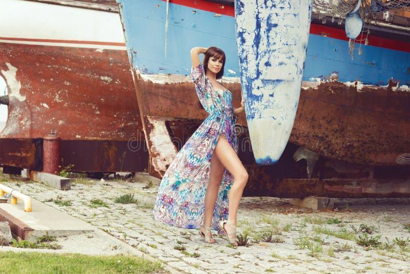 摆在老生锈的小船前面的美好,肉欲和性感的时装模特儿 图库摄影