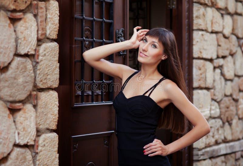 摆在老葡萄酒墙壁和门附近的俏丽的少女室外生活方式画象,佩带在都市背景的黑礼服 免版税库存照片