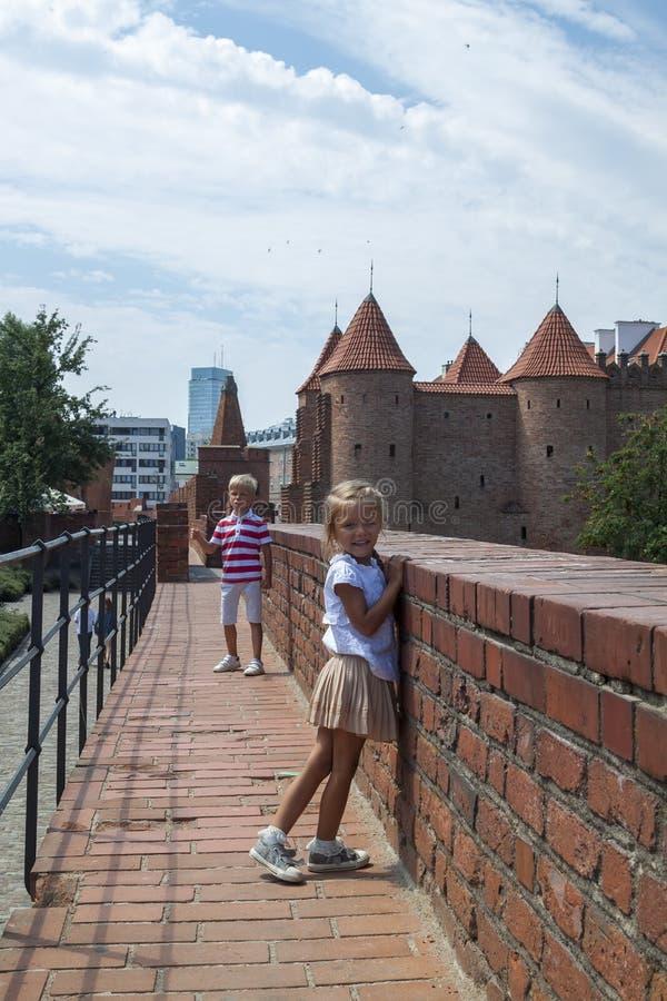 摆在老街道上的年轻美丽的男孩和女孩室外画象  老华沙,波兰,夏天 图库摄影