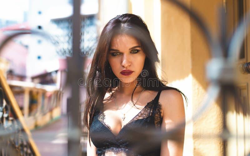 摆在老街道背景的性感的女用贴身内衣裤的热情的女孩  免版税图库摄影