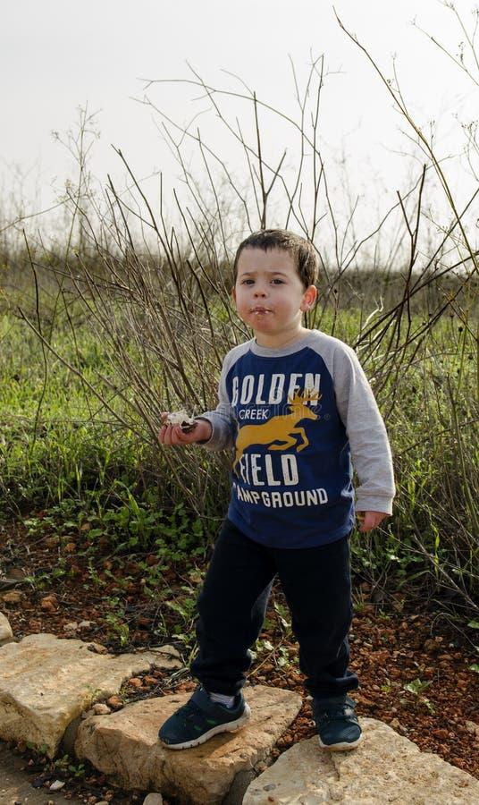 摆在自然吃Krembo的小孩 免版税图库摄影